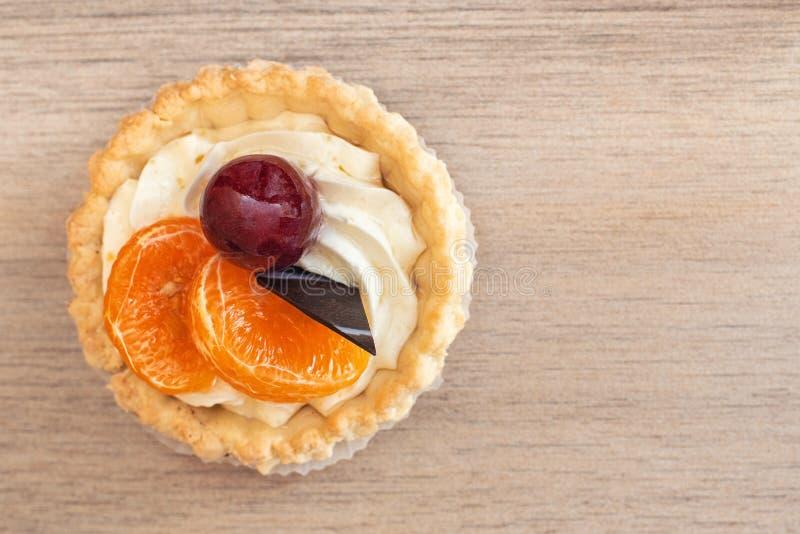 Panier de gâteau dans le sable avec de la crème, mandarine un chocolat sur la table en bois légère Vue supérieure images stock