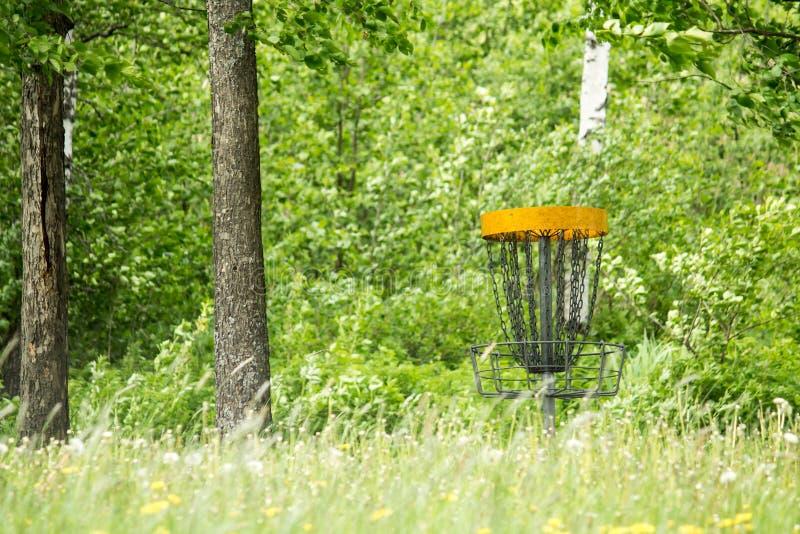 Panier de golf de frisbee derrière l'herbe brouillée photo stock