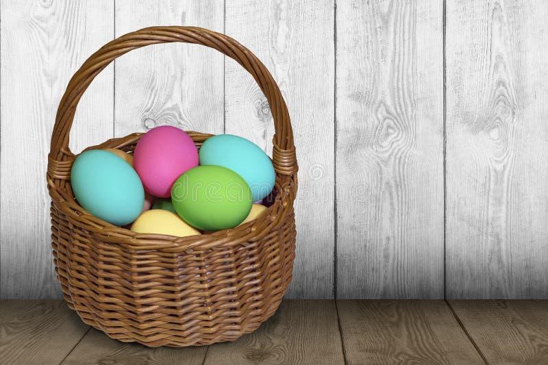 Panier de Pâques rempli d'oeufs peints au-dessus de table en bois photos libres de droits