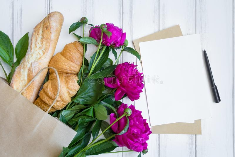 Panier de papel con el pan fresco, los cruasanes, las flores y la endecha del plano de la lista de compras, visión superior de la imagen de archivo