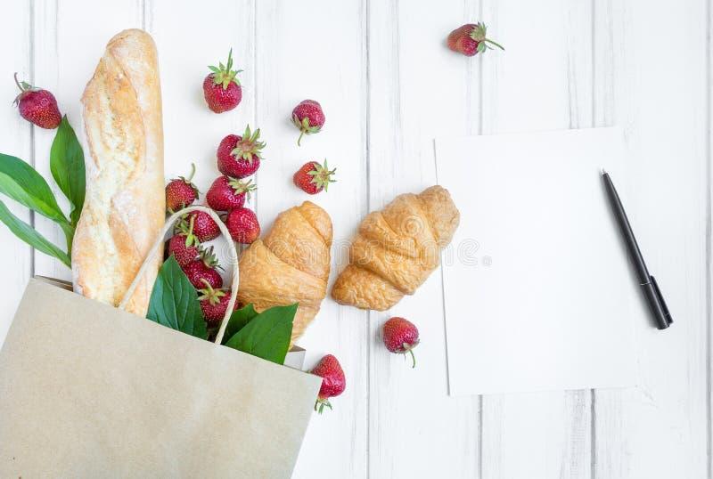 Panier de papel con pan fresco, cruasanes, las fresas y la endecha del plano de la lista de compras, visión superior fotografía de archivo
