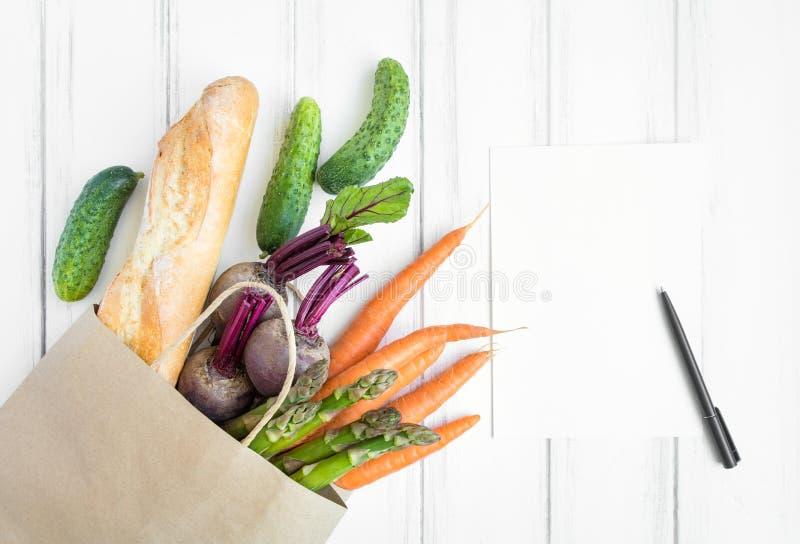 Panier de papel con pan fresco y verduras Endecha plana, visión superior foto de archivo libre de regalías