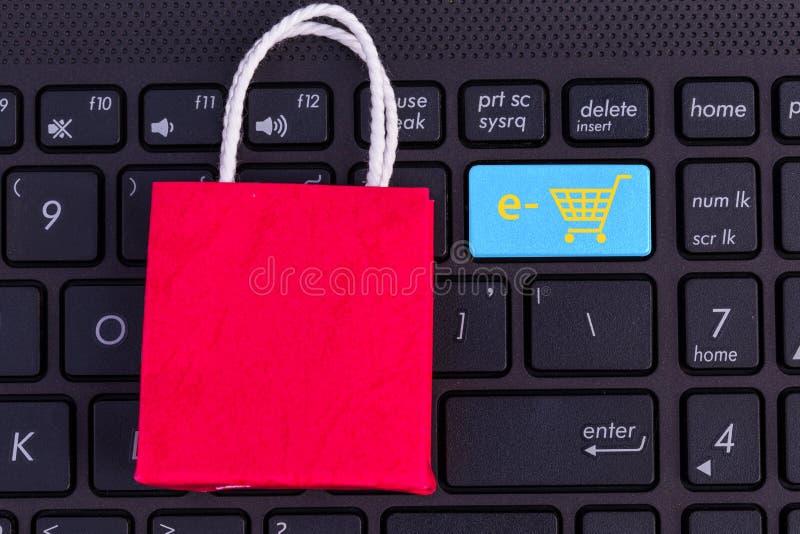 Panier de papel rojo en el teclado del ordenador portátil Ideas sobre sh en línea foto de archivo libre de regalías