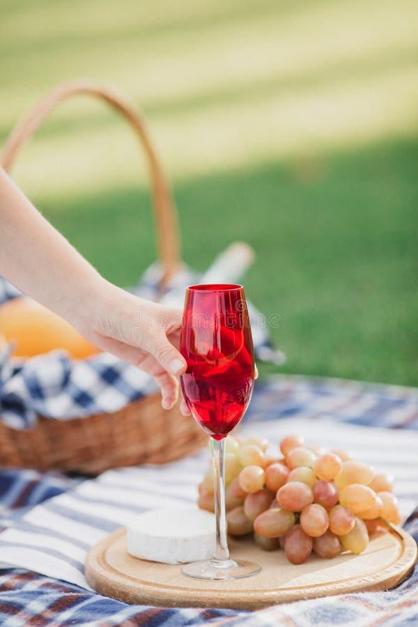 Panier de pique-nique avec les boissons, la nourriture et le fruit sur l'extérieur d'herbe verte en parc d'été images stock