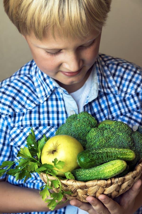 Panier de prise de garçon avec les légumes verts photo libre de droits