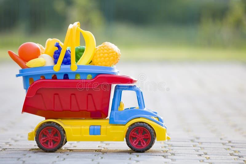 Panier de transport de jouet de camion coloré en plastique lumineux de voiture avec des fruits et légumes de jouet dehors le jour photographie stock libre de droits