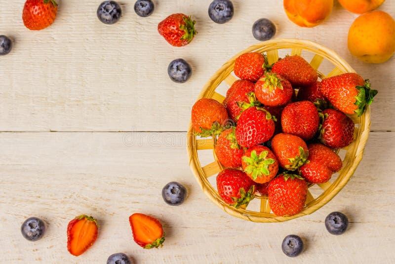 Panier des fraises sur une vieille table en bois blanche et des baies au bord des myrtilles dans un verre, abricots desktop images libres de droits
