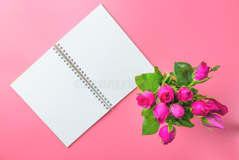 Panier des roses roses décoratives avec le bloc-notes vide sur la vue supérieure f photos libres de droits