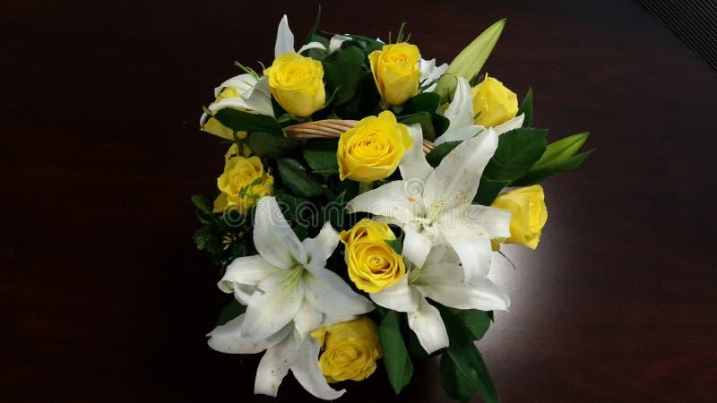 Panier des roses jaunes et des lis blancs - puissance des fleurs photo libre de droits
