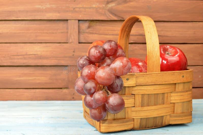 Panier en bois avec les pommes et le groupe de raisins rouges image stock