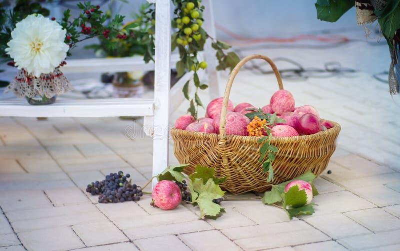 Panier en bois complètement des jamboses, des raisins et des fleurs dans un backg photographie stock libre de droits