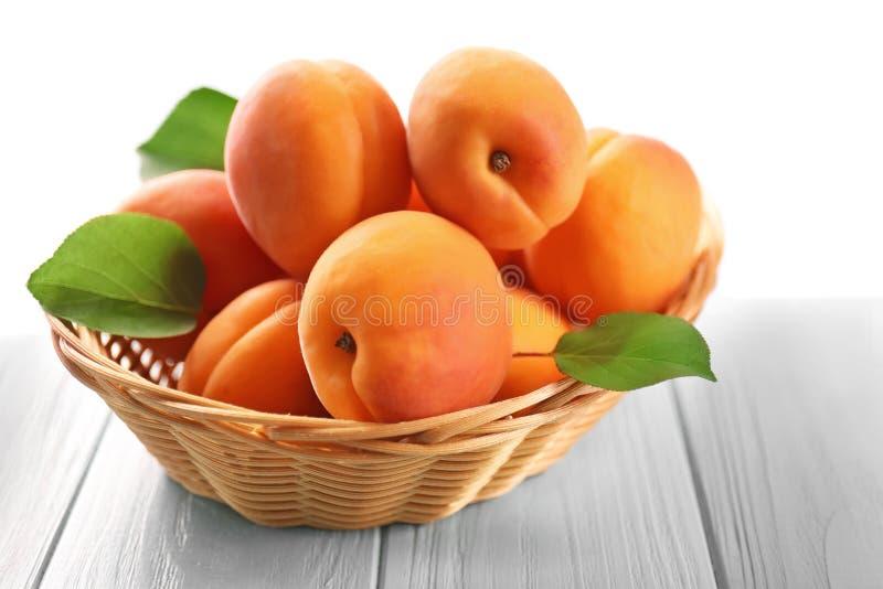 Panier en osier avec les abricots frais photo libre de droits
