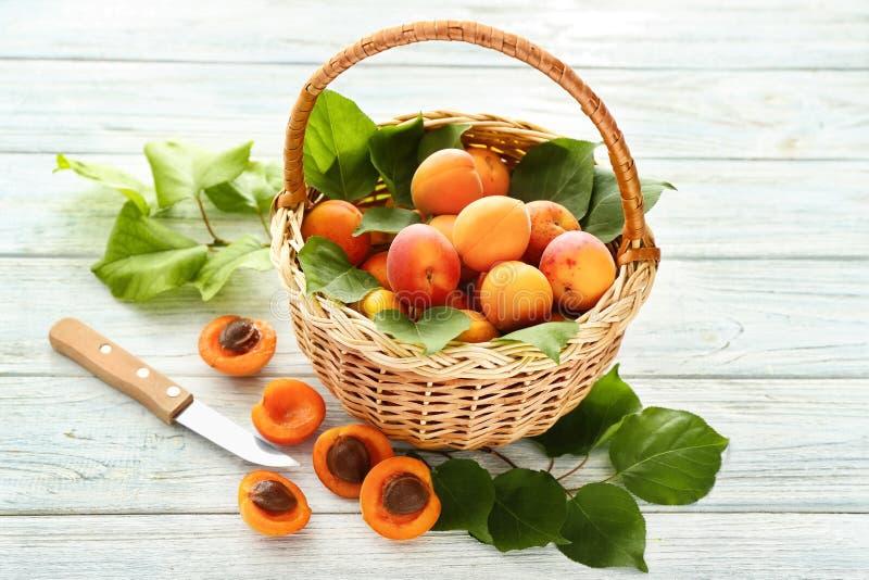 Panier en osier avec les abricots frais sur la table en bois photo libre de droits