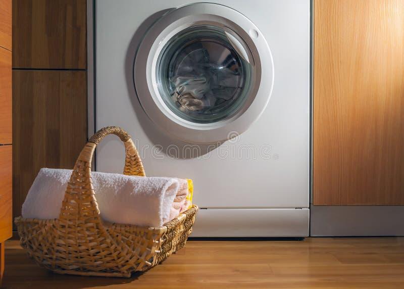 Panier en osier avec les serviettes propres sur le plancher par la machine à laver avec la blanchisserie Buanderie int?rieure de  photographie stock libre de droits