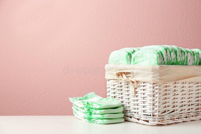 Panier en osier et couches-culottes jetables sur la table sur le fond de couleur, l'espace pour le texte photos libres de droits