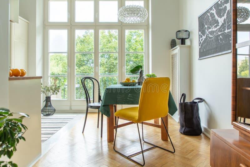 Panier grande al lado de una tabla de madera con un mantel verde y de un cuenco de limones en una cocina y un comedor naturales imágenes de archivo libres de regalías