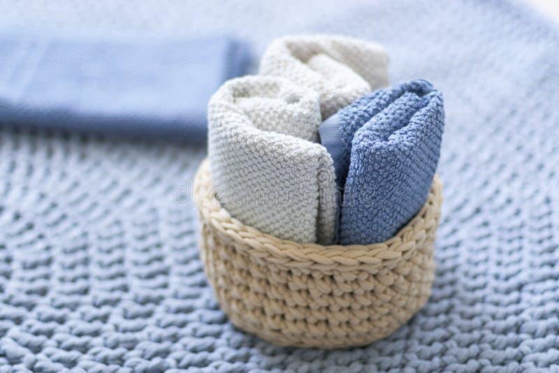 Panier tricoté de couleur claire avec des serviettes sur le fond bleu photos libres de droits