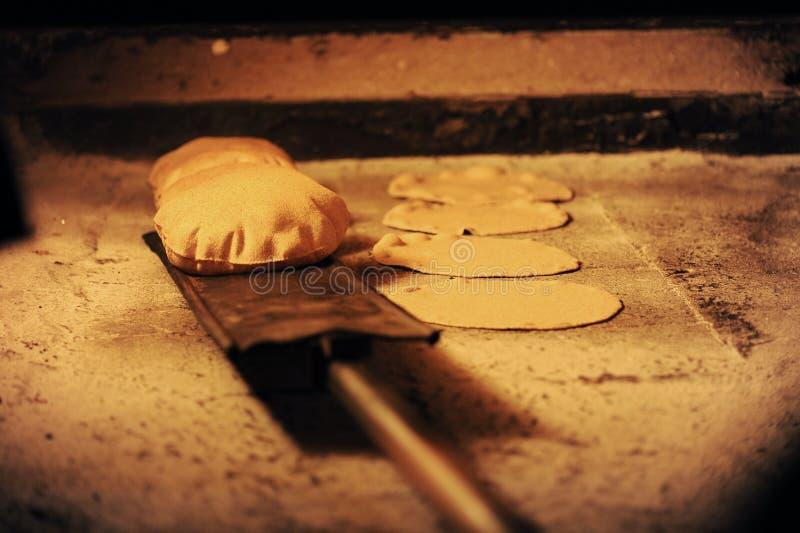 Panieren Sie Backen in einem geöffneten traditionellen Brennholzofen lizenzfreies stockfoto