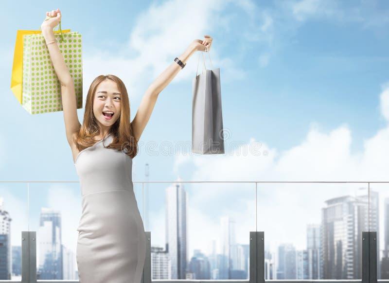 Panieres que llevan de la mujer china feliz en la ciudad imagen de archivo libre de regalías