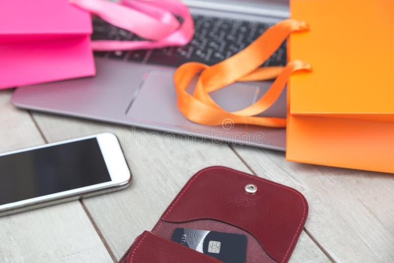 Panieres, tarjeta de crédito, ordenador portátil en el escritorio fotografía de archivo