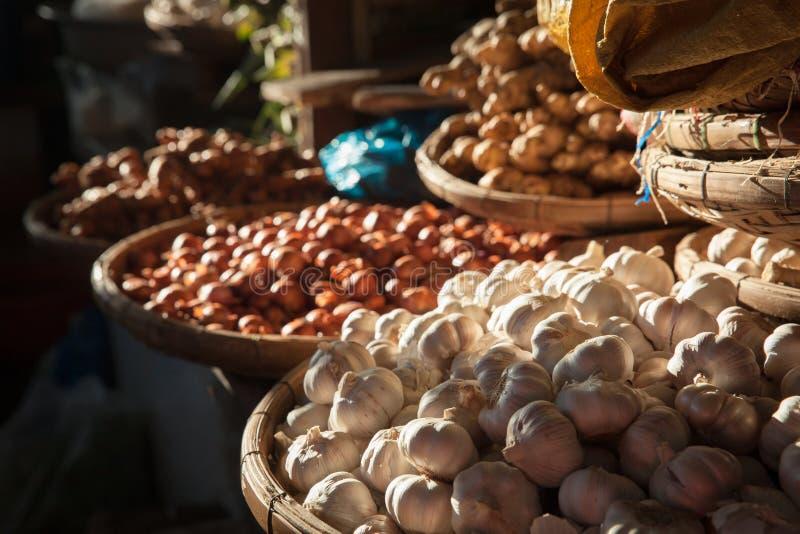 Paniers avec l'ail et les oignons au marché photo stock