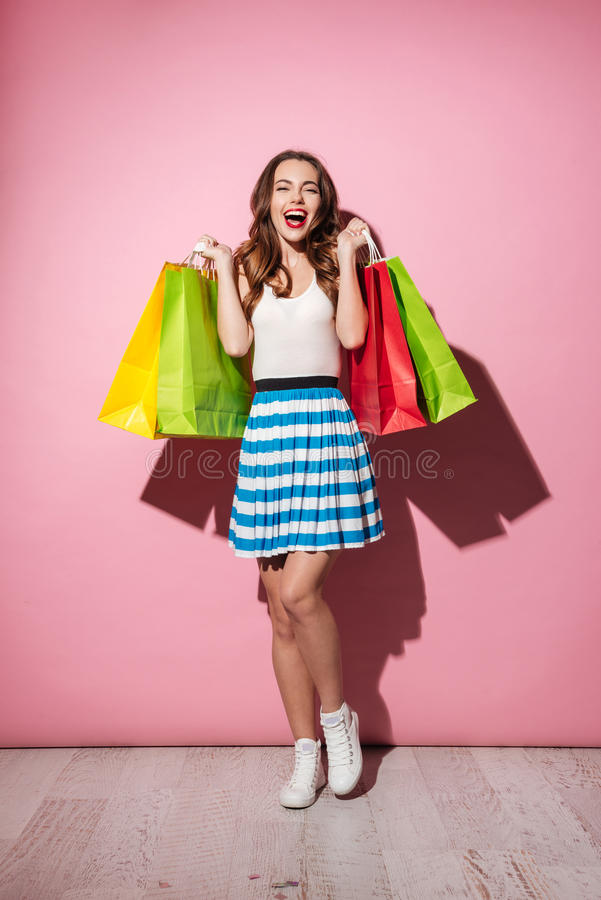 Paniers colorés de participation shopaholic enthousiaste heureuse de femme image stock