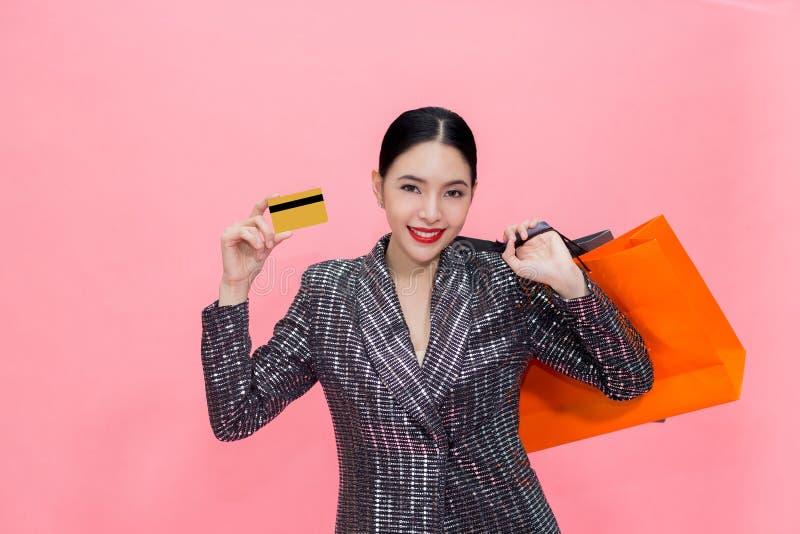Paniers de transport de jeune femme asiatique élégante et tenir la carte de crédit Belle femme à la mode d'isolement au-dessus du photographie stock