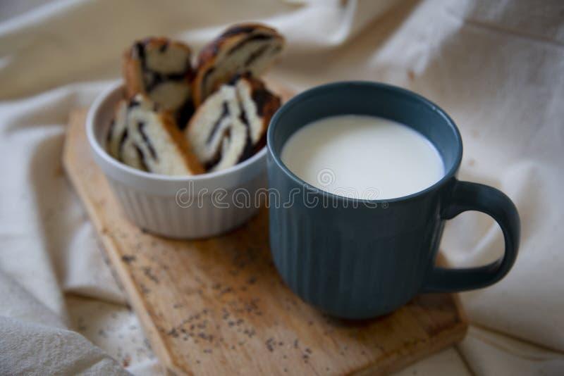 Panini affettati con il materiale da otturazione del seme di papavero e una tazza di latte fotografia stock libera da diritti
