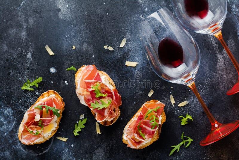 Panini al prosciutto aperti, rucola e formaggio a pasta dura, serviti sul supporto di legno con i aglass di vino rosso sul vecchi immagini stock