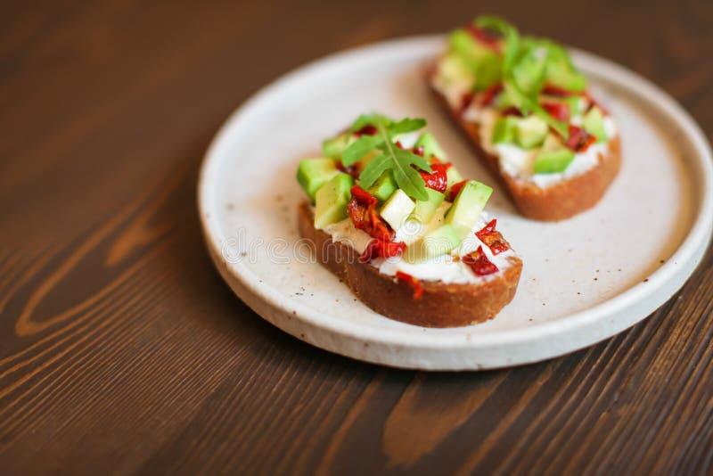 Panini appeni preparato con l'avocado, il pane di segale, i pomodori, il concetto di alimento sano, la nutrizione e gli acidi gra immagini stock