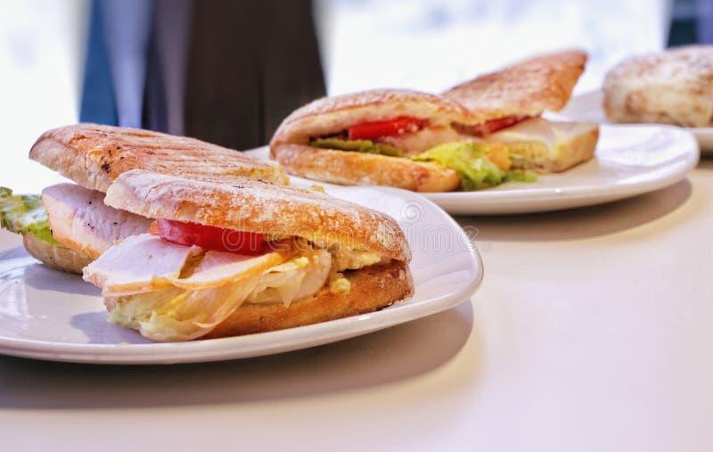 Panini caldi deliziosi con il tacchino, l'insalata di pollo ed i pomodori, taglio in piatti sulla tavola fotografia stock