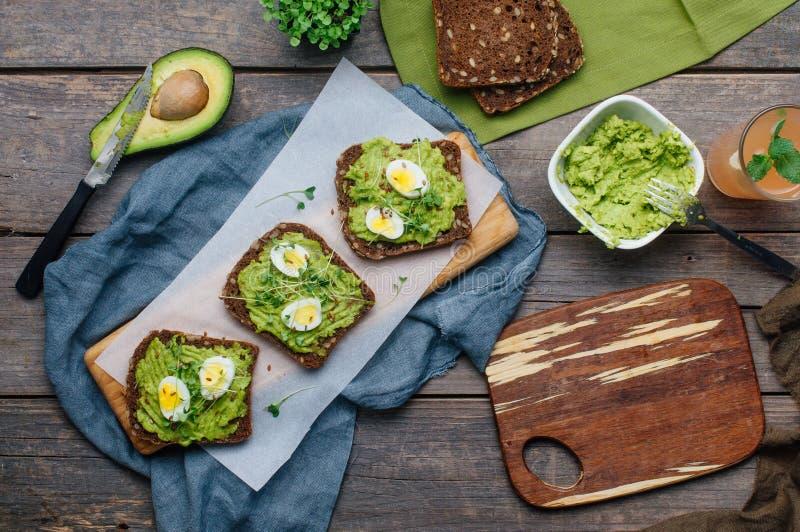 Panini casalinghi con il avokado, le uova di quaglia ed i germogli del ravanello fotografia stock