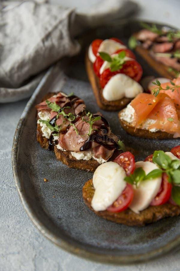 Panini con arrosto di manzo e rucola, salmone e cumino, mozzarella e pomodori su pane nero immagini stock