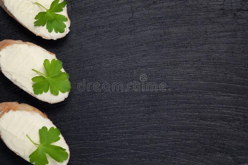 Panini con formaggio cremoso su un bordo scuro dell'ardesia - modello per progettazione con il posto per testo fotografie stock libere da diritti