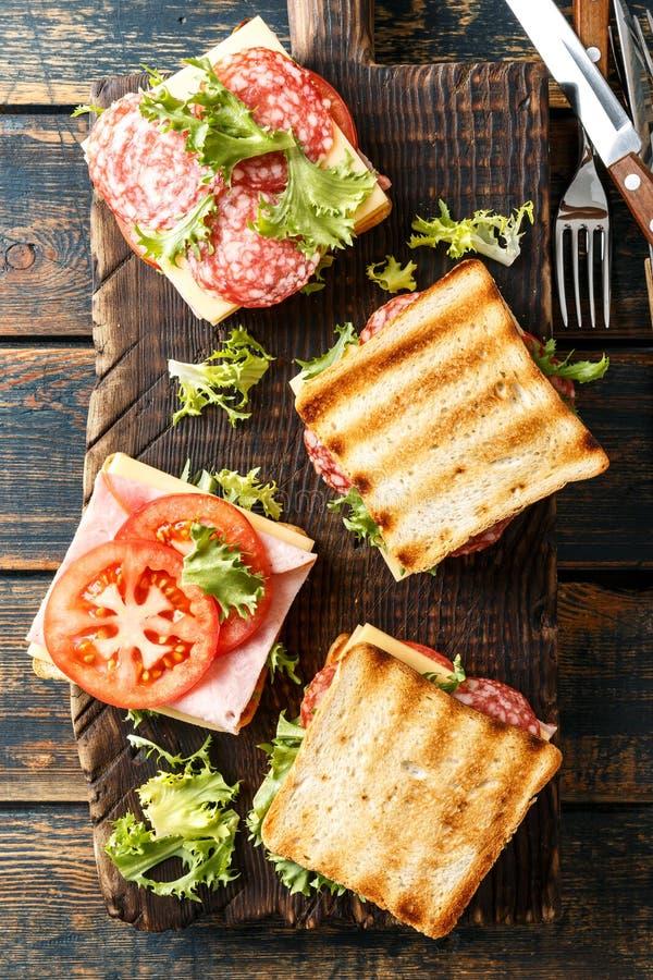 Panini con i pomodori arrostiti e la lattuga del formaggio del salame del prosciutto del pane tostato fotografia stock
