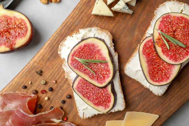 Panini con il formaggio cremoso maturo e del fico sul bordo di legno fotografia stock