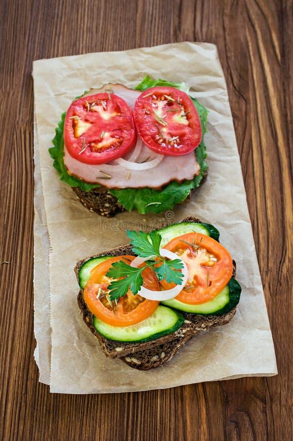 Panini con il prosciutto, il formaggio ed i pomodori fotografia stock