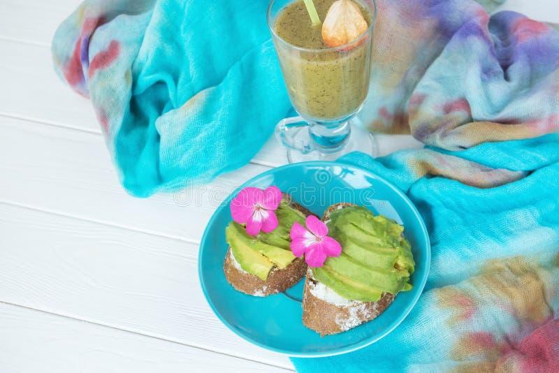 Panini con pane grezzo ed avocado e frullati naturali verdi fatti dal kiwi e dai verdi Alimento sano Natura morta, l'umore fotografie stock libere da diritti