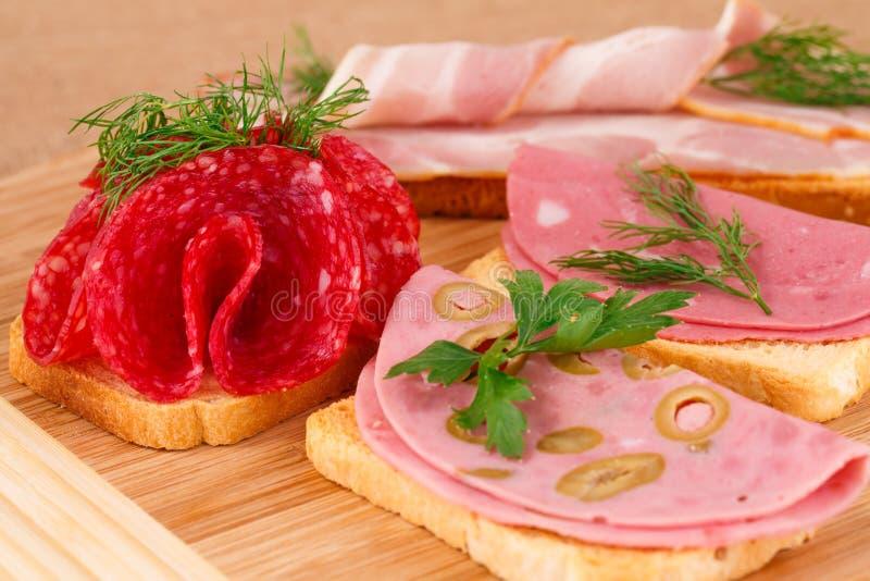 Panini con salame, bacon e mortadella immagine stock