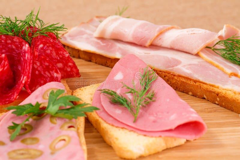 Panini con salame, bacon e mortadella fotografia stock