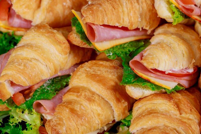 Panini dei croissant con lattuga, formaggio, i pomodori ed il prosciutto fotografia stock libera da diritti