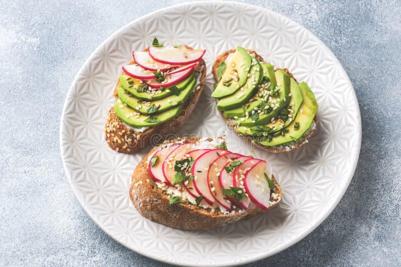 Panini del pane del cereale con la ricotta, l'avocado fresco ed il ravanello immagine stock