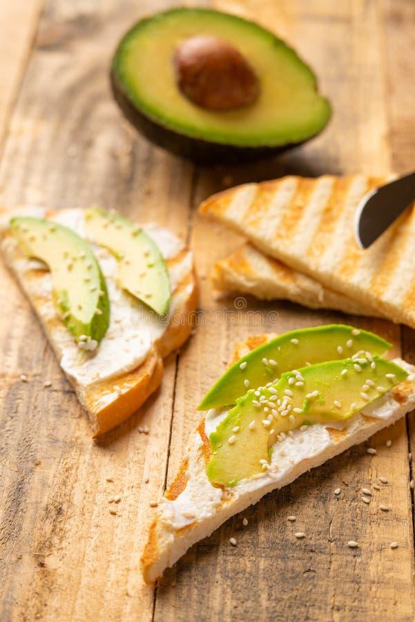 Panini dell'avocado, alimento sano e pulito del formaggio di Filadelfia con pane tostato e sesamo, della prima colazione di matti fotografia stock libera da diritti