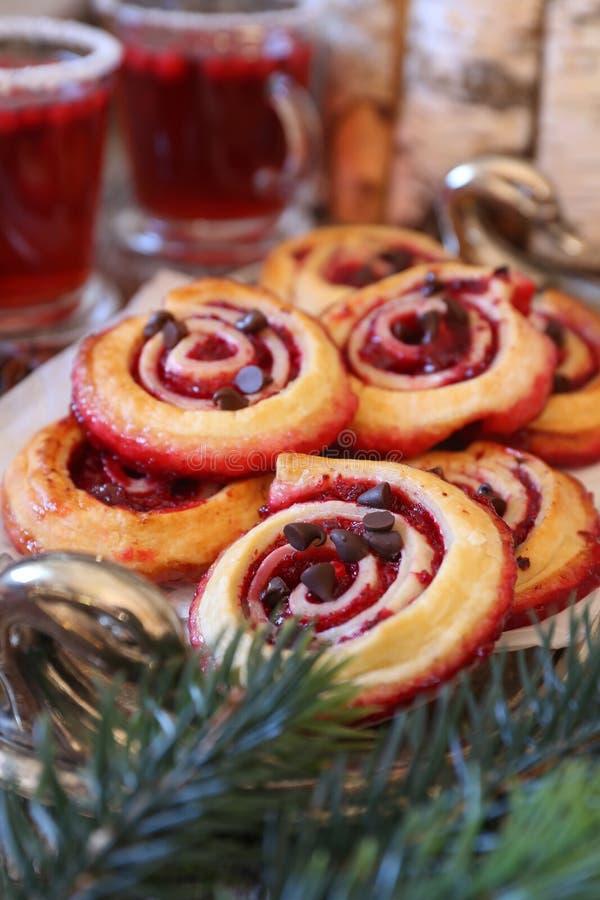Panini dolci del rotolo del mirtillo rosso con le gocce di cioccolato e due tazze della bevanda di frutta del mirtillo rosso immagine stock