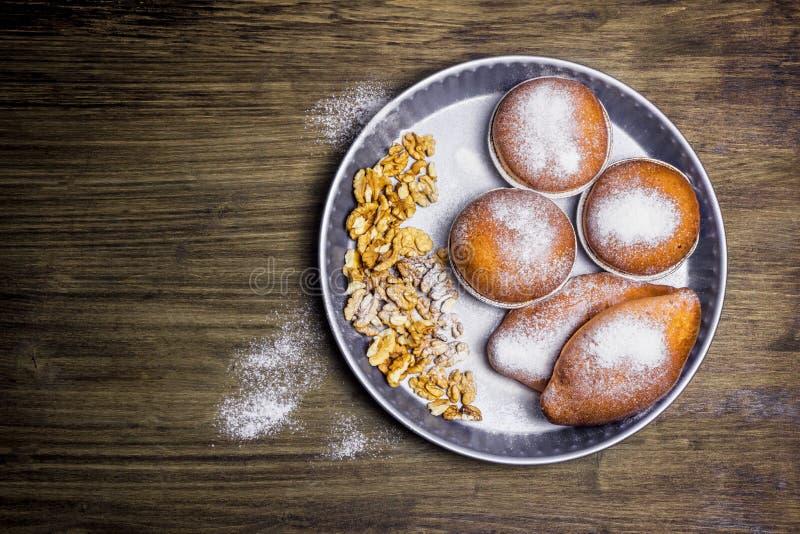 Panini e noci saporiti in zucchero in polvere su un piatto del metallo fotografia stock libera da diritti