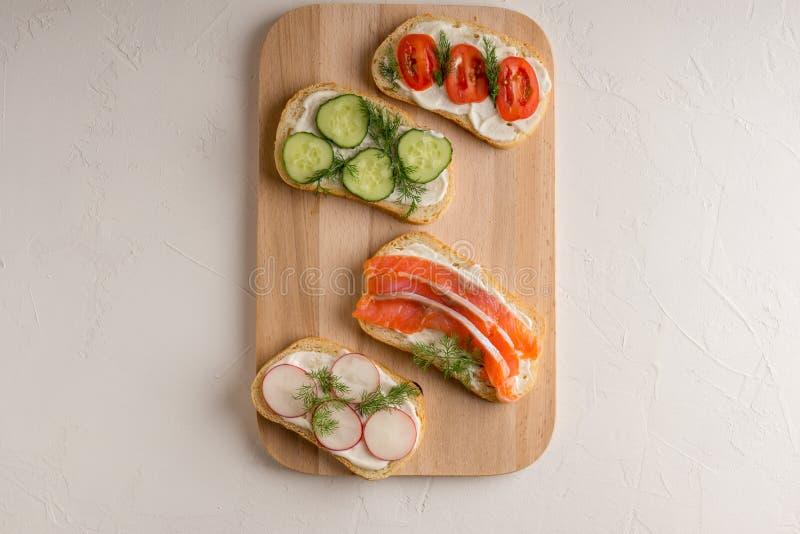 Panini freschi con il salmone, il cetriolo, i pomodori, gli avocado ed i verdi fotografie stock libere da diritti