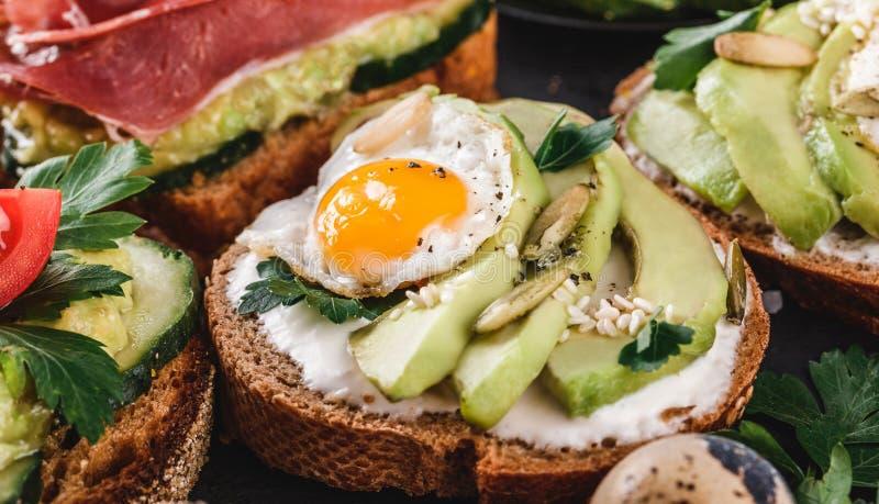 Panini interi del pane del grano con l'uovo di quaglia, l'avocado, le erbe ed i semi fritti su fondo nero Cibo pulito, vegano in  fotografia stock libera da diritti