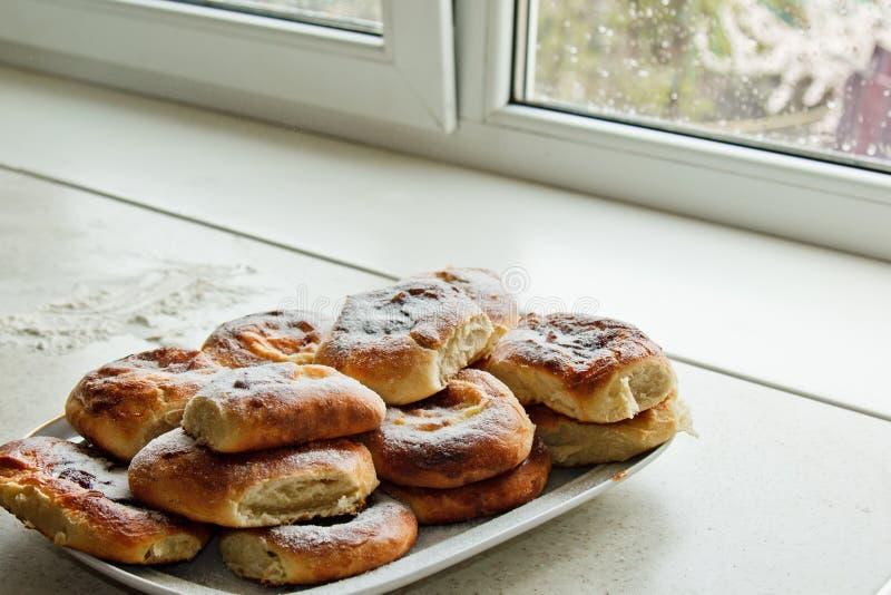 Panini in piatti pieni delle torte di formaggio di recente al forno con la ricotta sul tavolo da cucina Cottura della cottura Pre fotografia stock