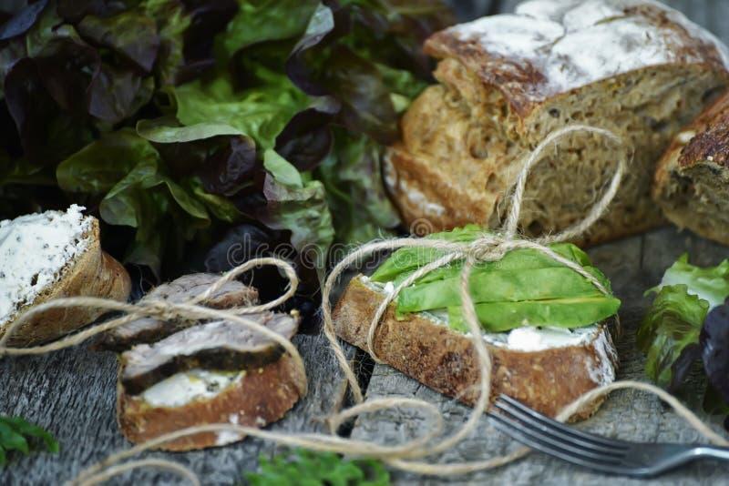 Panini puri con carne al forno e gli avocado su un fondo di legno approssimativo Alimento semplice dell'azienda agricola fotografia stock