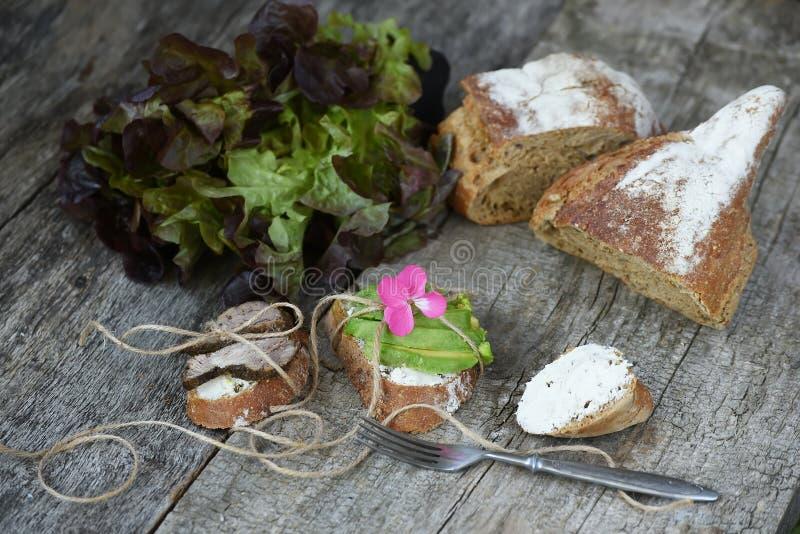 Panini puri con carne al forno e gli avocado su un fondo di legno approssimativo Alimento semplice dell'azienda agricola immagine stock